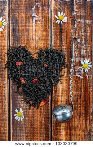 Vintage strainer near dry leaves of black tea make in heart on wooden background. Tea concept. Tea leaves. Top view. Closeup. Love