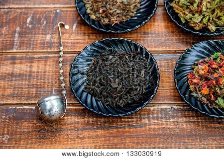Different kinds of tea on plates on wooden background near vintage strainer. Assortment of dry tea. Tea concept. Tea leaves. Top view. Closeup