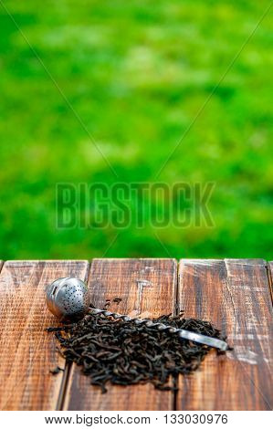 Vintage strainer with dry leaves of black tea on wooden table in garden and on nature background. Tea concept. Tea leaves. Top view. Closeup. Copy space