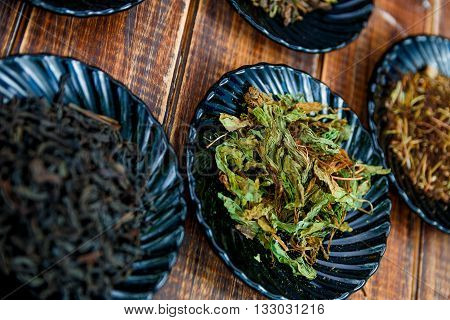 Green tea. Different kinds of tea on plates on wooden background. Assortment of dry tea. Tea concept. Tea leaves. Closeup