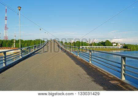 VELIKY NOVGOROD RUSSIA - MAY 24 2016. Footbridge across the Volkhov river and people walking along in spring sunny evening