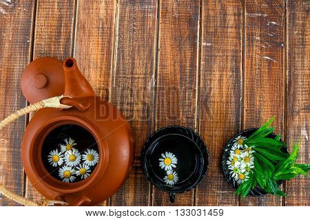Open brown teapot with flower of chamomile near black cup of tea and plate with fresh mint and chamomile on wooden background. Tea concept. Frame copy space.