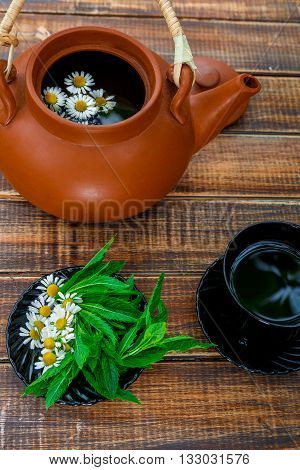 Open brown teapot with flower of chamomile near black cup of tea and plate with fresh mint and chamomile on wooden background. Closeup. Tea concept.