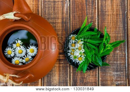 Open brown teapot with flower of chamomile near black plate with fresh mint and chamomile on wooden background. Closeup. Tea concept.