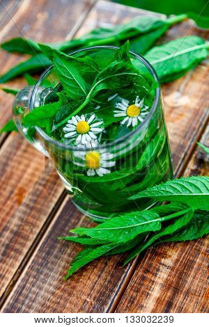 A cup of mint tea with chamomile on a wooden background. herbal tea with chamomile and fresh mint leaves on table. Closeup.