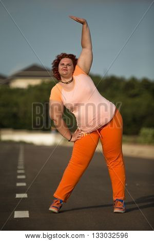 Plus size woman stretching legs for warming up before running in city park