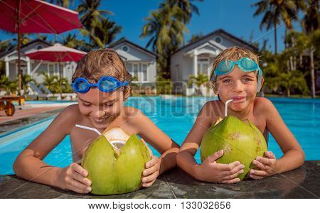 two children with coconuts in swimming pool