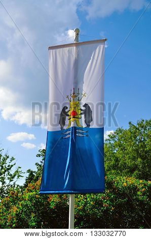 VELIKY NOVGOROD RUSSIA - JUNE 3 2016. Flag of Veliky Novgorod on a flagpole with coat of arms of the city closeup view