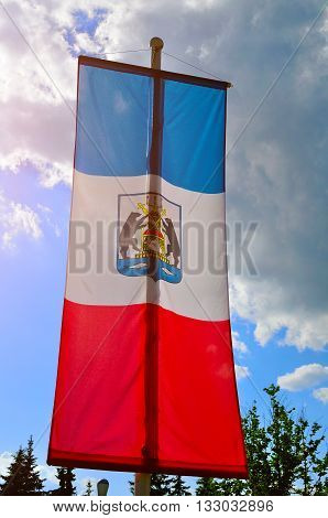 VELIKY NOVGOROD RUSSIA - JUNE 3 2016. Flag of Veliky Novgorod region on a flagpole with coat of arms of the region closeup view