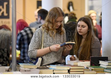 VILNIUS - FEBRUARY 26: people choose books at the indoor book market on February 26 2016 in Vilnius Lithuania. Vilnius is the capital of Lithuania and its largest city.