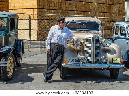 Napier New Zealand - November 19 2014: Driver dressed in 1930s attire would chauffeur paying passengers around the quaint Art Deco seaside town of Napier on the North Island of New Zealand. Vintage cars are iconic sight of Napier street.