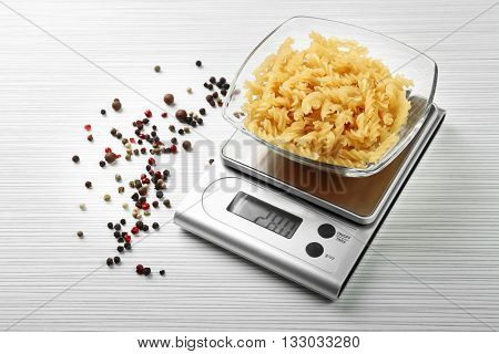 Pasta with digital kitchen scales on wooden background