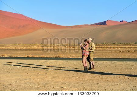 Couple of tourist man and woman taking a pictures on the smartphones in Sossusvlei at sunrise. Namib-Naukluft National Park Namibia Africa