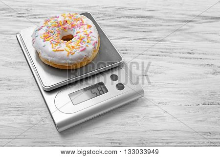 Donut with digital kitchen scales on wooden background