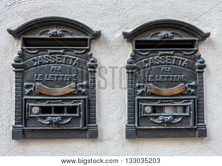 Two traditional Italian iron retro postbox for letters hanging on the wall of the house.