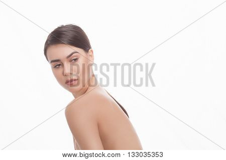 Portrait of beautiful shirtless or topless lady looking away over white background. Studio shot. Cosmetic surgery concept.