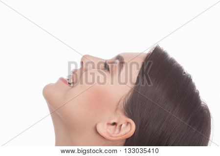 Face of young woman with clean skin isolated on white background. Happy lady smiling and looking upwards in studio.
