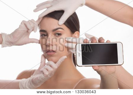 Examining face concept. Closeup portrait of mobile phone with blank screen in front of beautiful lady during examination of her face by cosmetologists.