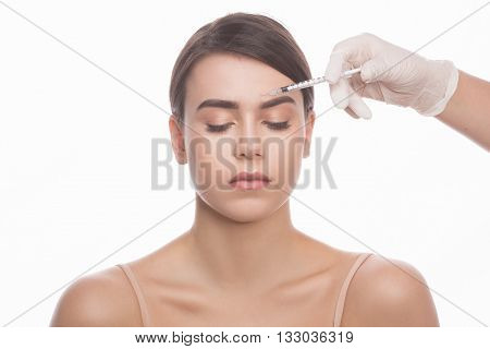 Medical injection. Portrait of beautiful young woman keeping eyes closed while doctors hands in gloves making injection in her face isolated on white.