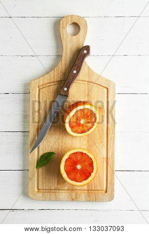 Halved juicy Sicilian orange on wooden board
