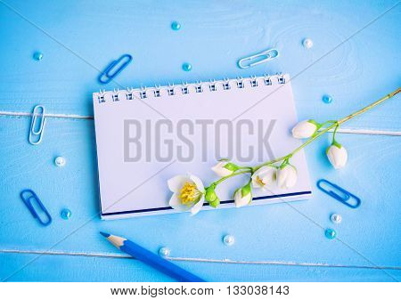 Blank notepad, blue pencil, clips, beads and jasmine flowers on painted wooden background