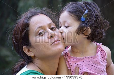Daughter kissing her mother on cheek. Outdoors.  Mother's day, family, childhood and people concept.