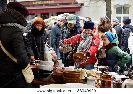 VILNIUS LITHUANIA - MARCH 6: Unidentified people trade typical lithuanian clay pots in annual traditional crafts fair - Kaziuko fair on March 6 2016 in Vilnius Lithuania