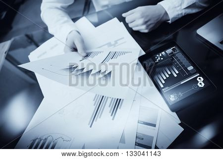 Investment manager working process.Photo trader work market report documents.Using electronic devices.Work graphic icons, stock exchanges reports screen.Business project startup.Horizontal, black white