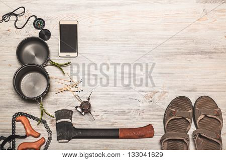 Equipment of hiking gear on a wooden floor background