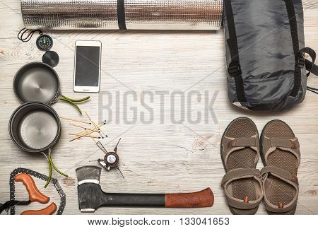 Overhead view of hiking gear laid out for a trip on a rustic wood floor. Gear include compass phone tent ax gas burner matches shoes.