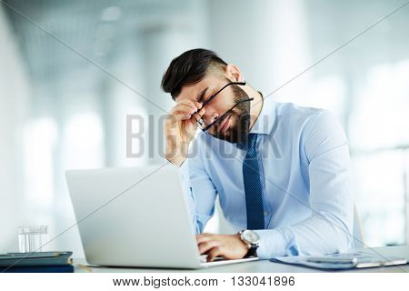 Businessman at his workplace tired of work