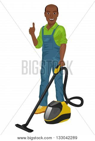 African american man in green coveralls posing with a vacuum cleaner and giving thumbs up