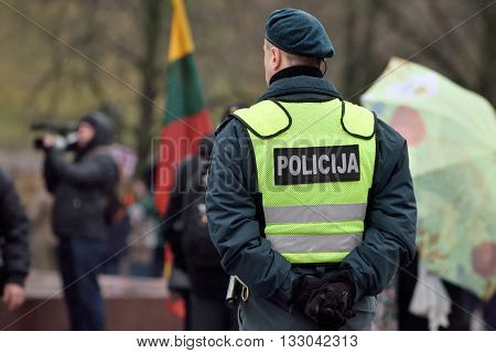 VILNIUS LITHUANIA - MAR 11: Police officer on duty in a nationalist rally at Gedimino Avenue on Re-Establishment of Independence Day on March 11 2016 in Vilnius Lithuania
