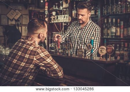 Handsome bartender pouring a pint of beer to customer in a pub.