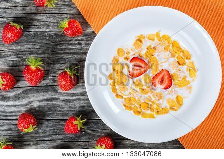 Corn flakes with milk and strawberry in a white dish on an old rustic table studio lights top view