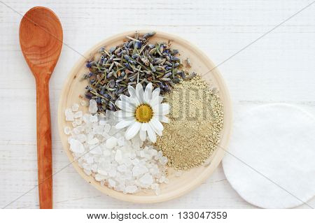 Blend of cosmetic clay, salt, lavender herb, chamomile, facial mask skincare  natural ingredients preparation, wooden, top view background.