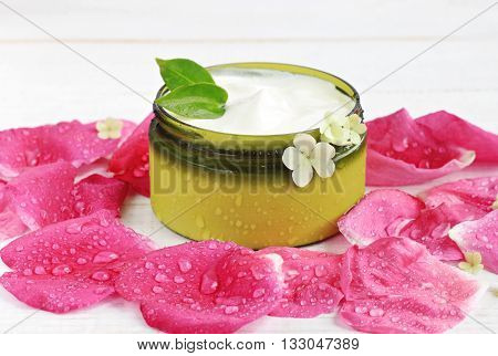White herbal facial cosmetic cream in jar, fresh pink wet rose petals scattered around, flowers.