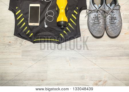Shoes and sports equipment on wooden floor. Top view flat lay.