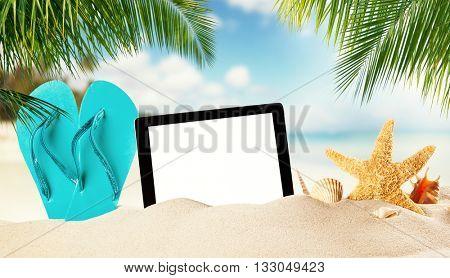 Summer concept with empty tablet display for copyspace. Blue flipflop and various kind of shells in sand. Palm leaves on foreground