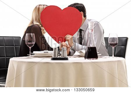 Affectionate couple sitting at a dinner table and kissing behind a red heart isolated on white background
