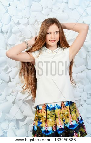 Cute girl with beautiful healthy long hair standing by a background of white flowers and smiling at camera. Healthy hair, haircare.