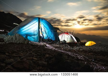 white adn blue Tents in the mountains at night