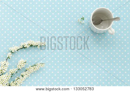 Empty cup with teaspoon on the polka dot background. Copy space