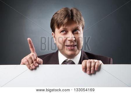 Portrait of adult businessman over blank space with index finger up.Studio shot