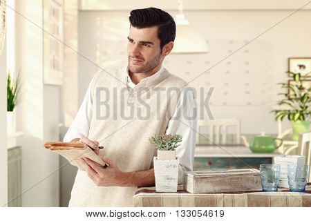 Handsome casual caucasian charming man at vintage italian home with newspaper in hand. Wearing sleeveless sweater, standing at dining room, wondering, thinking, smiling, bristly.