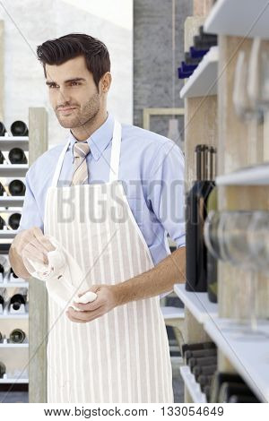 Young sommelier polishing wineglass, looking away, wearing apron.
