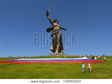 VOLGOGRAD RUSSIA - JUNE 12 2013: Boy and girl go to the aid of activists unfolding a large Russian flag in Day of Russia at the foot of the monument of Motherland Calls on Mamaev hill in Volgograd