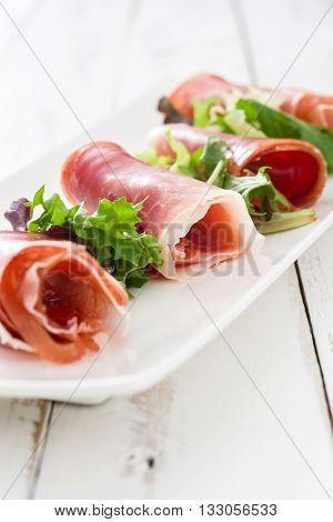 Spanish serrano ham on a white wooden table