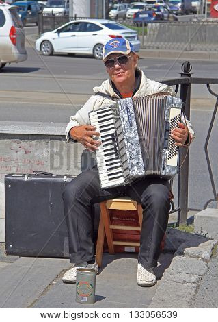 Yekaterinburg Russia - July 20 2015: street musician is playing accordion outdoor in Yekaterinburg Russia