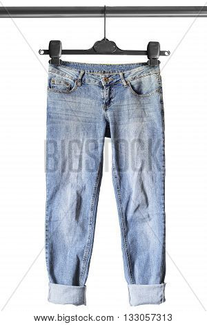 Blue casual jeans on clothes rack isolated over white